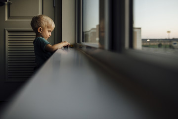 Side view of baby boy playing with toy cars on window sill at home during sunset