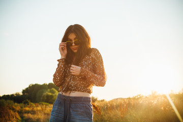 Young fashionable hippie woman in nature on summer day