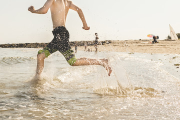 Low section of teenage boy running on shore at beach
