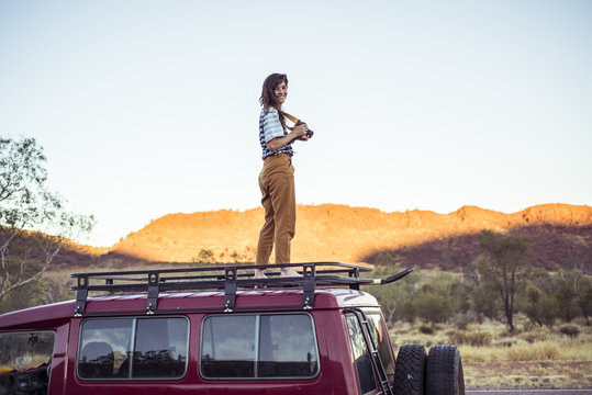 Smiling woman with camera standing on car roof against clear sky