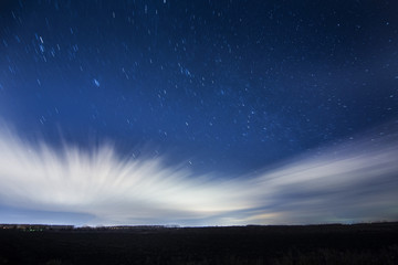 Stars breaking trough moving clouds