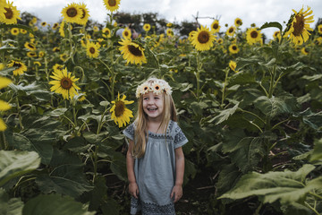 Cheerful girl standing amidst sunflowers at farm