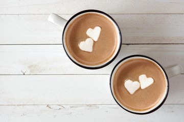 Two cups of hot chocolate with heart shaped marshmallows over a white wood background Wall mural