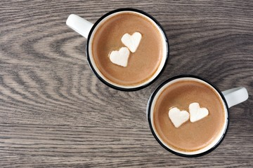 Two cups of hot chocolate with heart shaped marshmallows over a wooden background