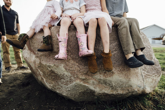 Low section of children sitting on rock