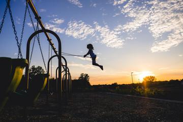 Full length of girl swinging on swing at playground during sunset