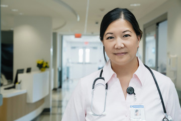 Portrait of confident female doctor with stethoscope in hospital lobby