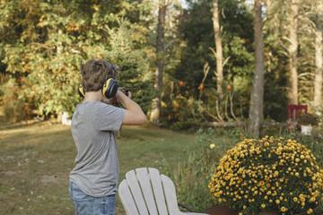 Side view of boy target shooting at backyard