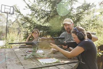Father and son looking at girl target shooting at backyard