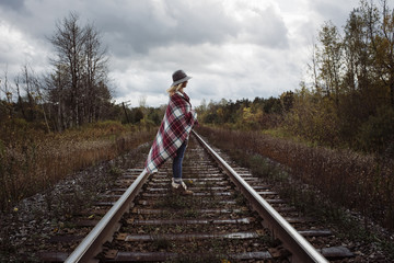 Side view of woman with blanket standing on railroad track against stormy clouds