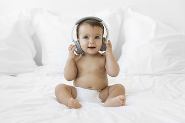 Baby girl with headphones sitting on bed