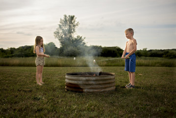 Sibling roasting marshmallows over fire pit