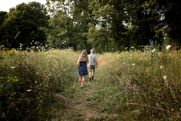 Rear view of siblings walking on field