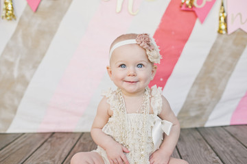 Smiling baby girl sitting on floorboard at birthday party