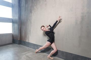 Ballerina movement in classic ballet posing near window