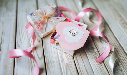 Marriage proposal concept. A wedding ring in a gift box on a wooden background. Valentine's Day. Festive decor.