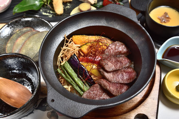 Japanese food - Sliced beef steak with fried vegetables cover rice