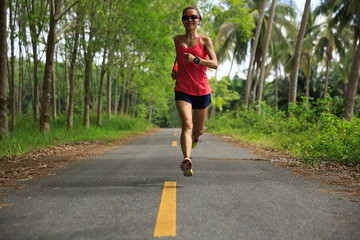 fitness woman runner running on tropical forest trail