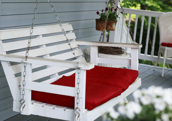 White porch swing with red cushions