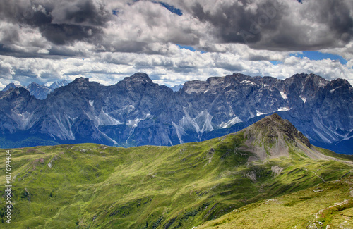 Sunlit gentle grassy slopes of Carnic Alps with limestone wall of ...