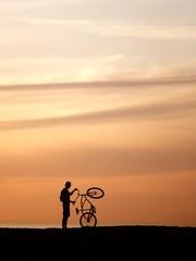 A man holding bike at the beach