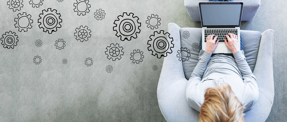 Gears with man using a laptop in a modern gray chair