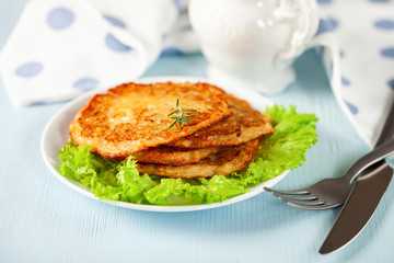 Potato hash brown with salad on a blue background. Selective focus. Rösti . Swiss national dish.