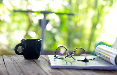 An open book, glasses and a blanket on the wooden background. orange, coffee cup, sunlight, selective focus.