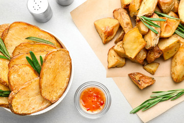 Composition with bowl of tasty rosemary potatoes on table