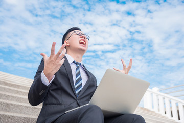 Young asian businessman working with notebook computer and screaming outdoor