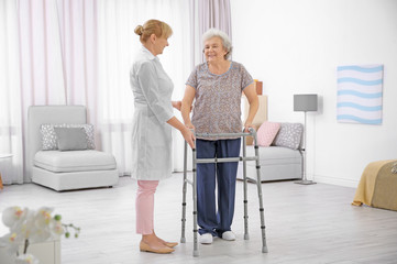 Senior woman with walking frame and caregiver at home
