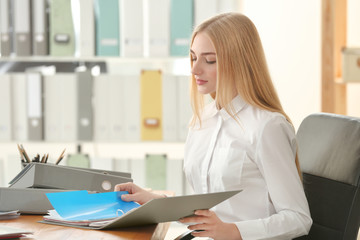 Young woman working with documents in archive