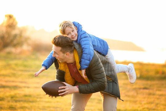 Father with little son playing rugby outdoors