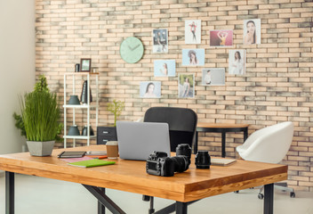 Interior of photographer office with laptop and camera on table