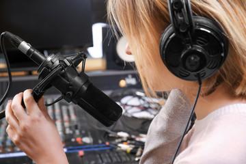 Female radio host broadcasting through microphone in studio