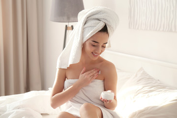 Young woman in white towel using cosmetic product at home