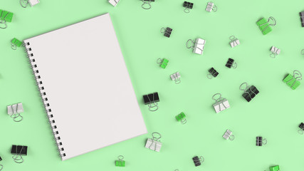 Blank spiral notebook with black, white and green binder clips on green table