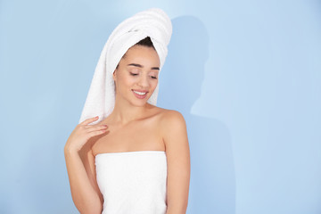 Young woman in white towel on color background