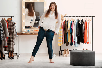 Beautiful overweight woman trying on jeans in boutique