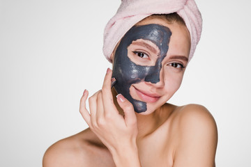happy girl applies cleansing mask on face