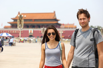 Happy multiracial couple on summer holidays having fun laughing together on Tianamen Square, Beijing, china. Asia travel. Chinese woman, Caucasian man, multiethnic tourists.