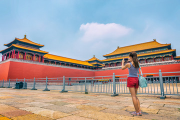 Woman taking mobile phone picture of Beijing tourist attraction, imperial architecture landmark. Asia travel, tourism destination popular attraction. Chinese girl.