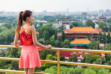 China summer travel. Woman tourist relaxing looking at view of famous chinese landmark, the forbidden City in Beijing. Jingshan Gongyuan park.