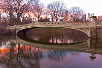 The Bow Bridge at beautiful winter sunrise in Central Park, New York City. The largest park bridge with reflection decorated by planting urns.