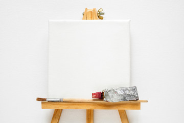 Canvas on easel, paint tube and  paintbrush. White canvas background. Top view. Flat lay. Copy space for text.
