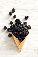 Blackberry explosion. Photo of blackberry in waffle cone on white wooden table. Top view. High resolution product.