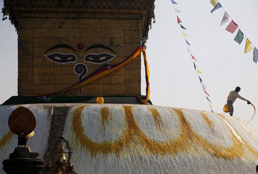 A man splashes paint on the dome of Swayambhunath Stupa in Kathmandu