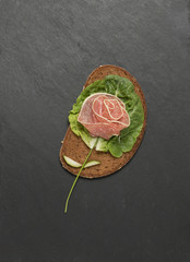 Rose made with sausage and bread on black background