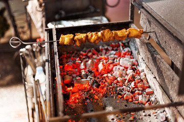 A barbecue skewer spinning on the grill. Fresh steaming meat BBQ. Street cart with grill.