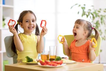 Funny children girls eating healthy food. Kids lunch at home or kindergarten.